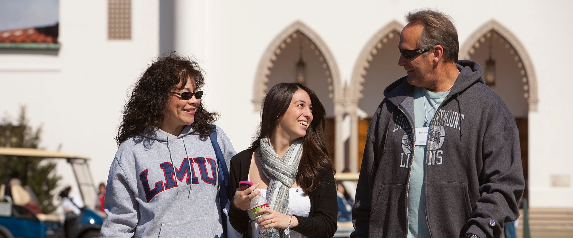 Two LMU parents with their student in front of chapel