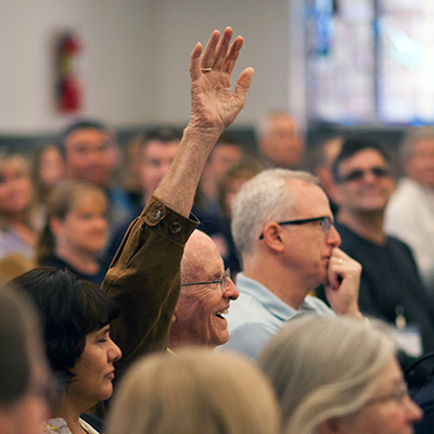 Parent raising their hand at an event
